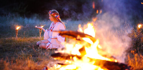White witch beside outdoor fire in pagan ritual
