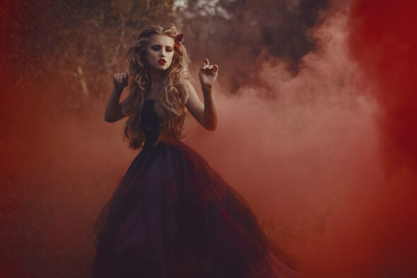 blonde witch in red dress against red smoky background