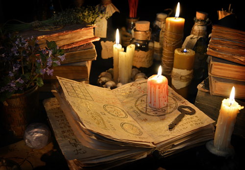 spell books and lit candles for witchcraft